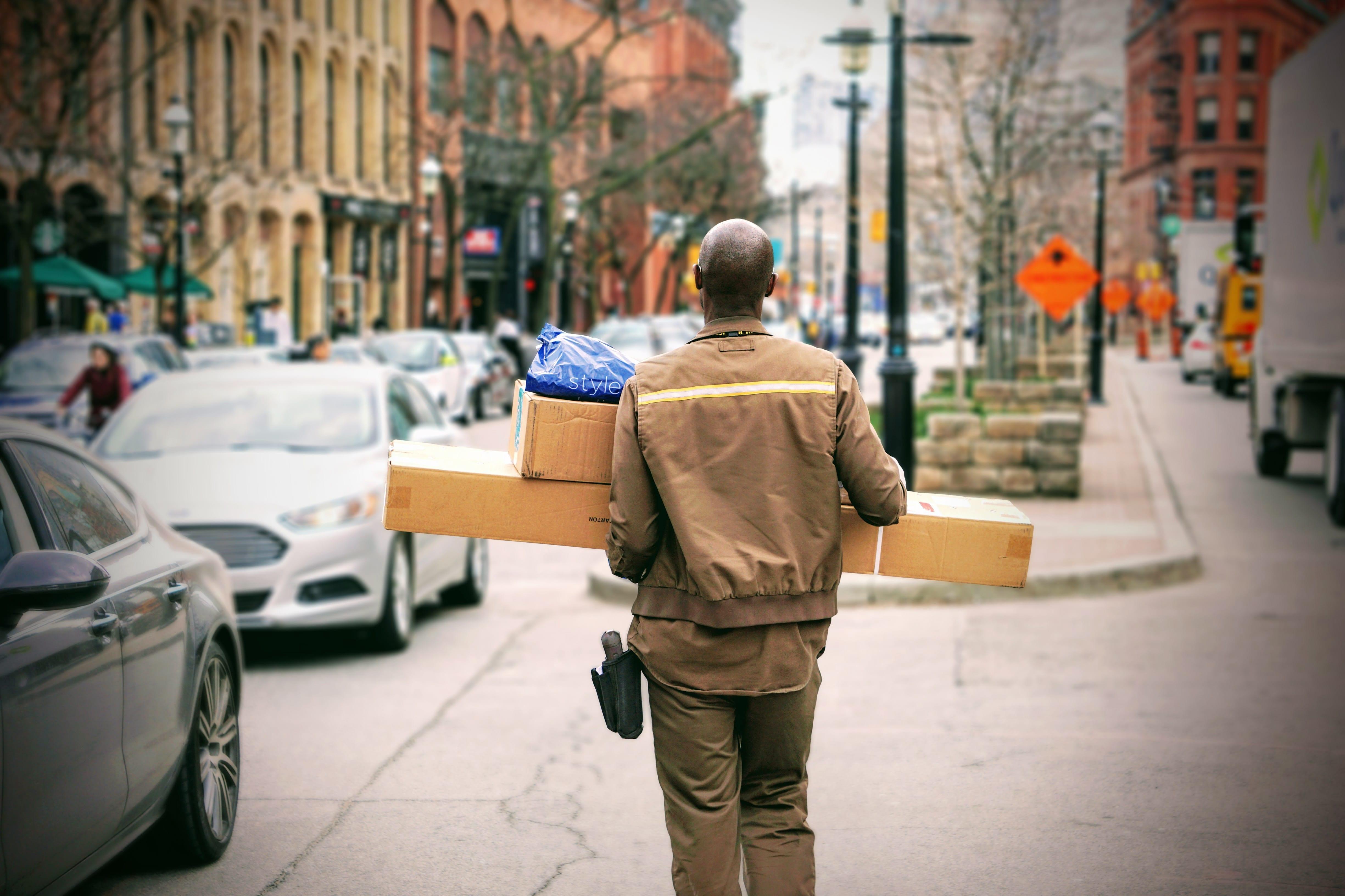 UPS employee in uniform carrying packages; image by Maarten van den Heuvel, via unsplash.com.