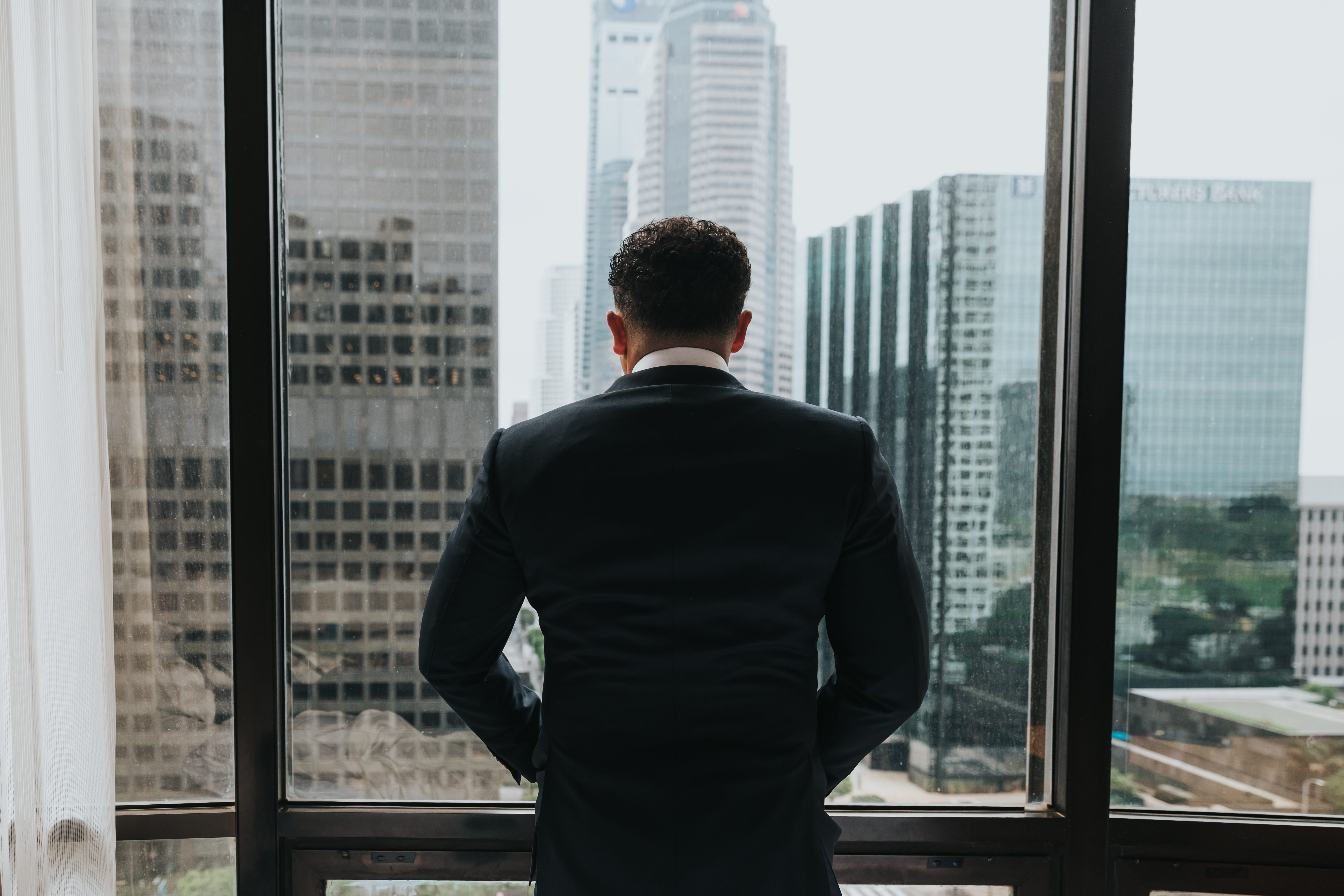 Man in suit, hands in pockets, looking out window of office building; image by Nathan Dumlao, via Unsplash.com.