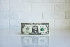 A one dollar bill standing on edge on a reflective white surface with a white brick wall as backdrop; image by NeONBRAND, via Unsplash.com.
