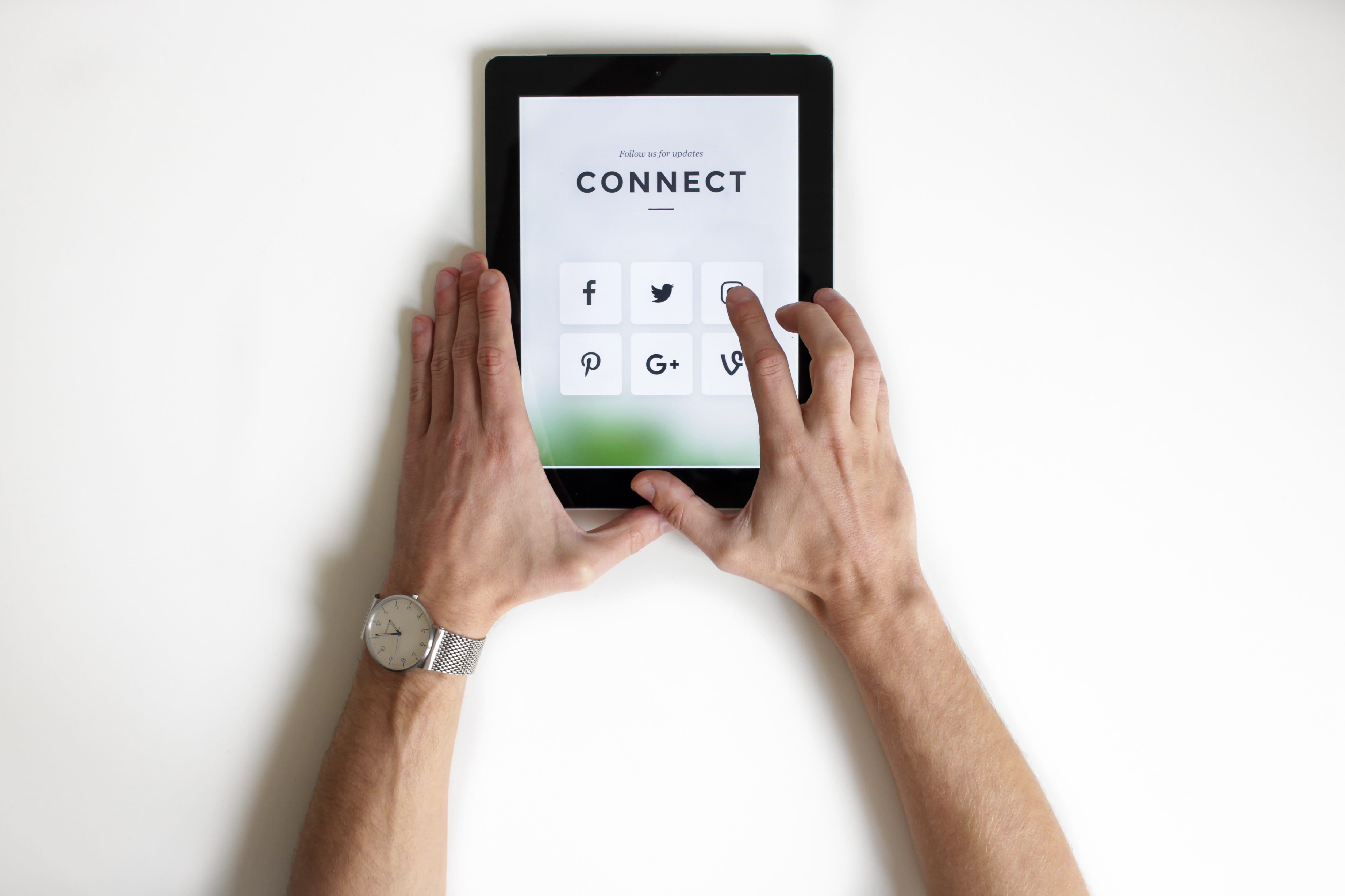 "Man holding a tablet with icons of various social networks and the word ""connect"" at the top; image by NordWood Themes, via Unsplash.com."