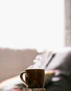 Shallow focus shot of hot coffee in mug; image by Tim Foster, via Unsplash.com.