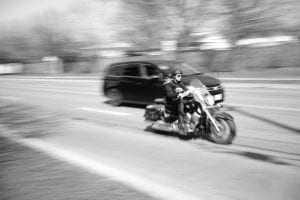 Man riding a motorcycle next to a minivan on the highway; image by VanveenJF, via unsplash.com.