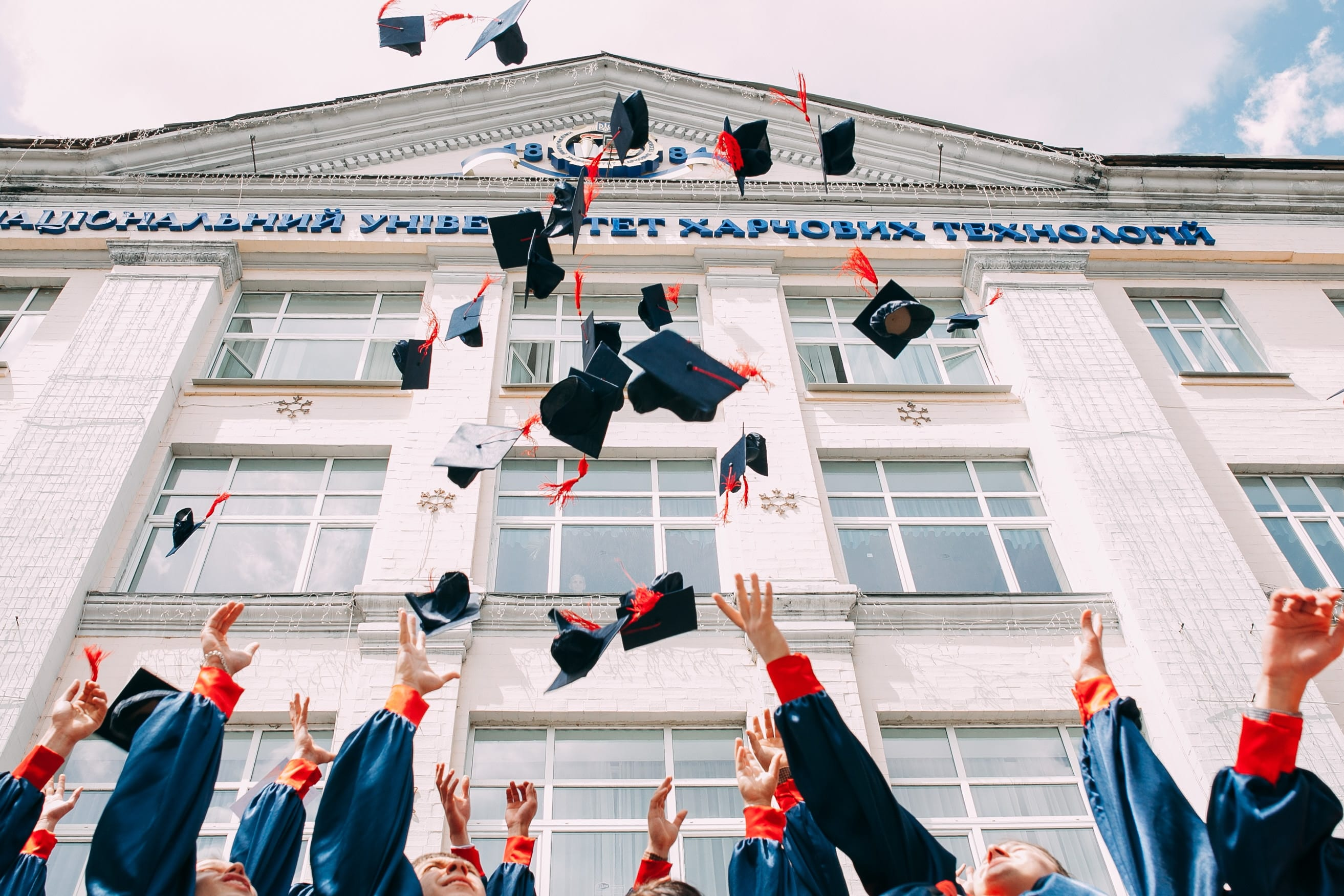 Graduates throwing their caps into the air; image by Vasily Koloda, via Unsplash.com.