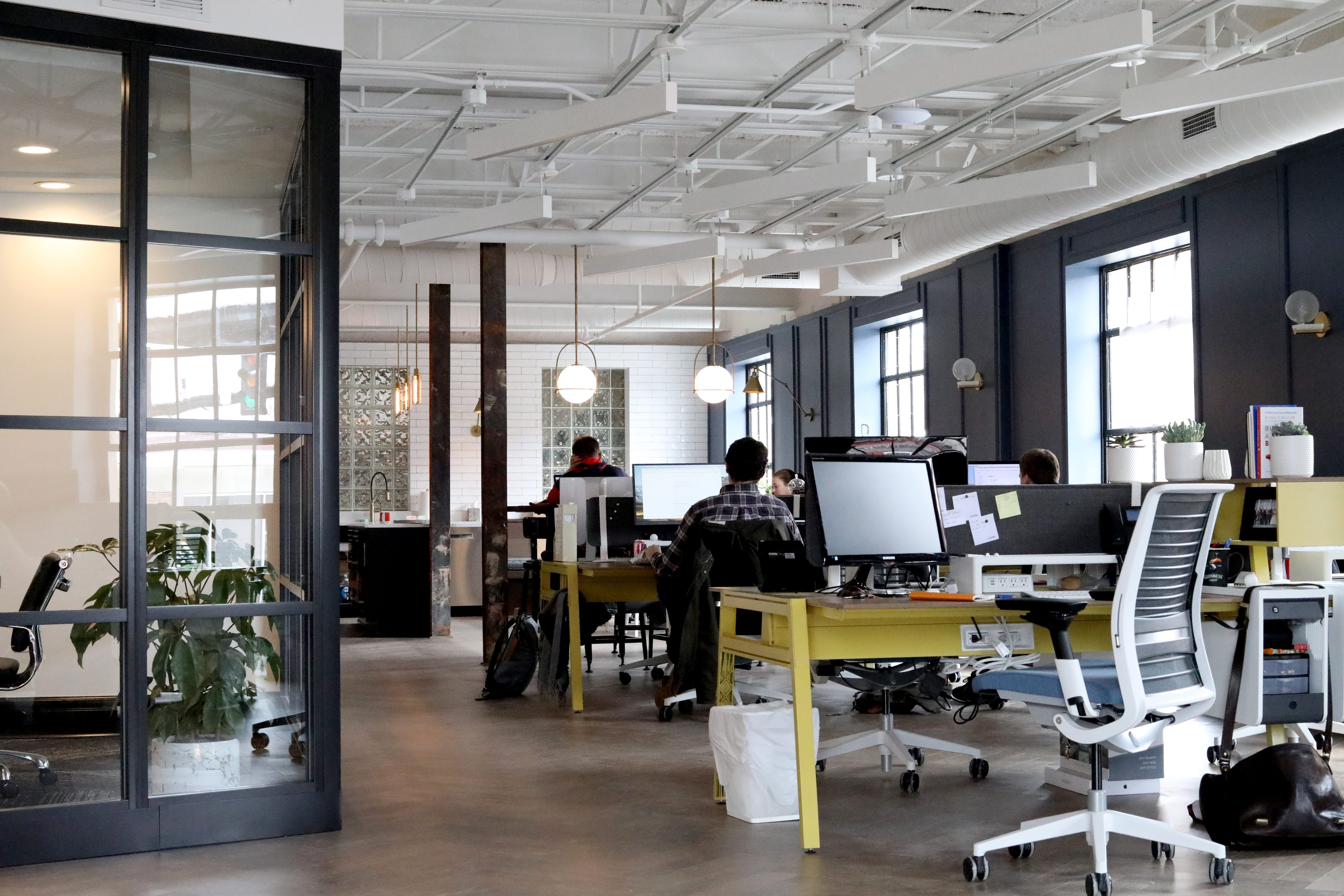 Open workspace with people sitting at desks; image by Venveo, via Unsplash.com.