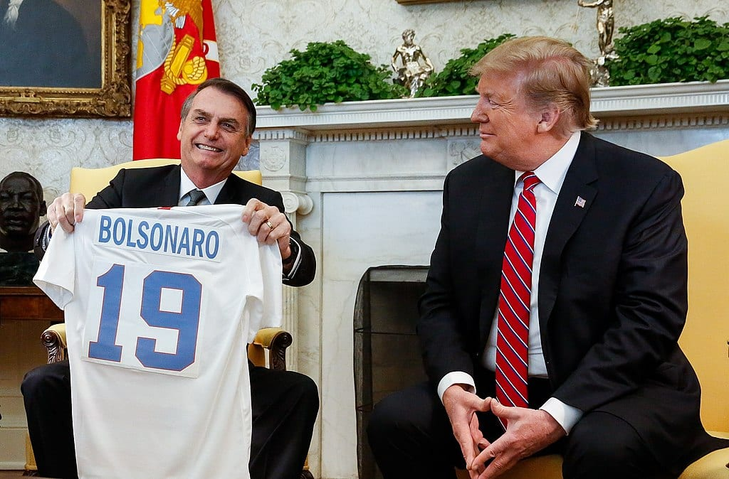 """Jair Bolsonaro holds up a sports jersey that says """"Bolsonaro 19"""" while sitting next to Donald Trump at the White House."""