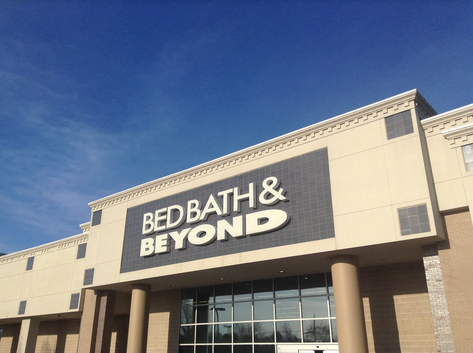 A Bed Bath & Beyond storefront, backed by a vivid blue sky.