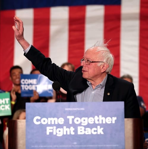 "Bernie Sanders, standing at a podium with his right arm upraised. A sign on the podium reads, ""Come Together, Fight Back."""