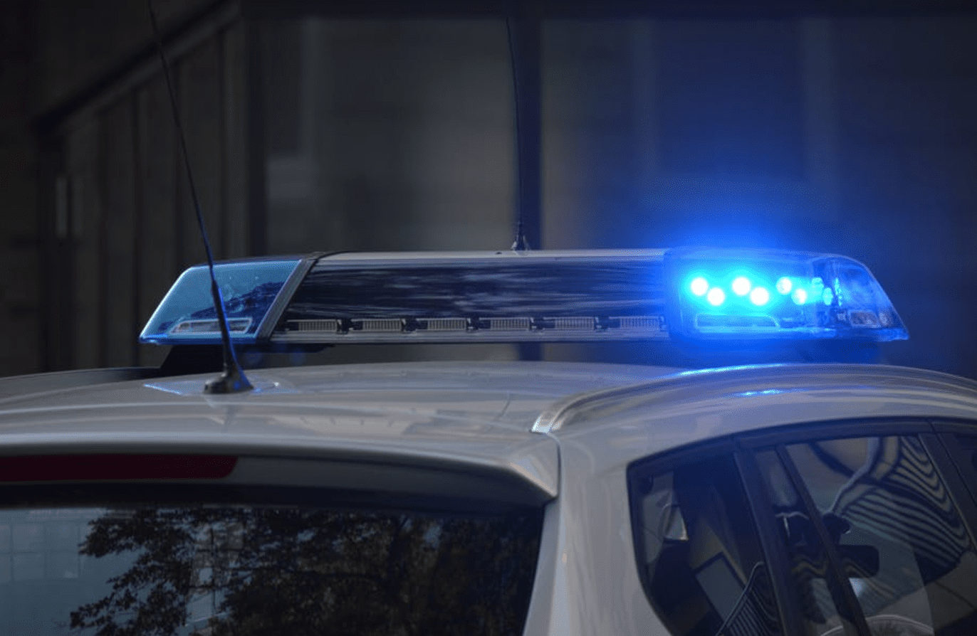 Roof of police car with blue light lit; image by Pixabay, via Pexels.com.