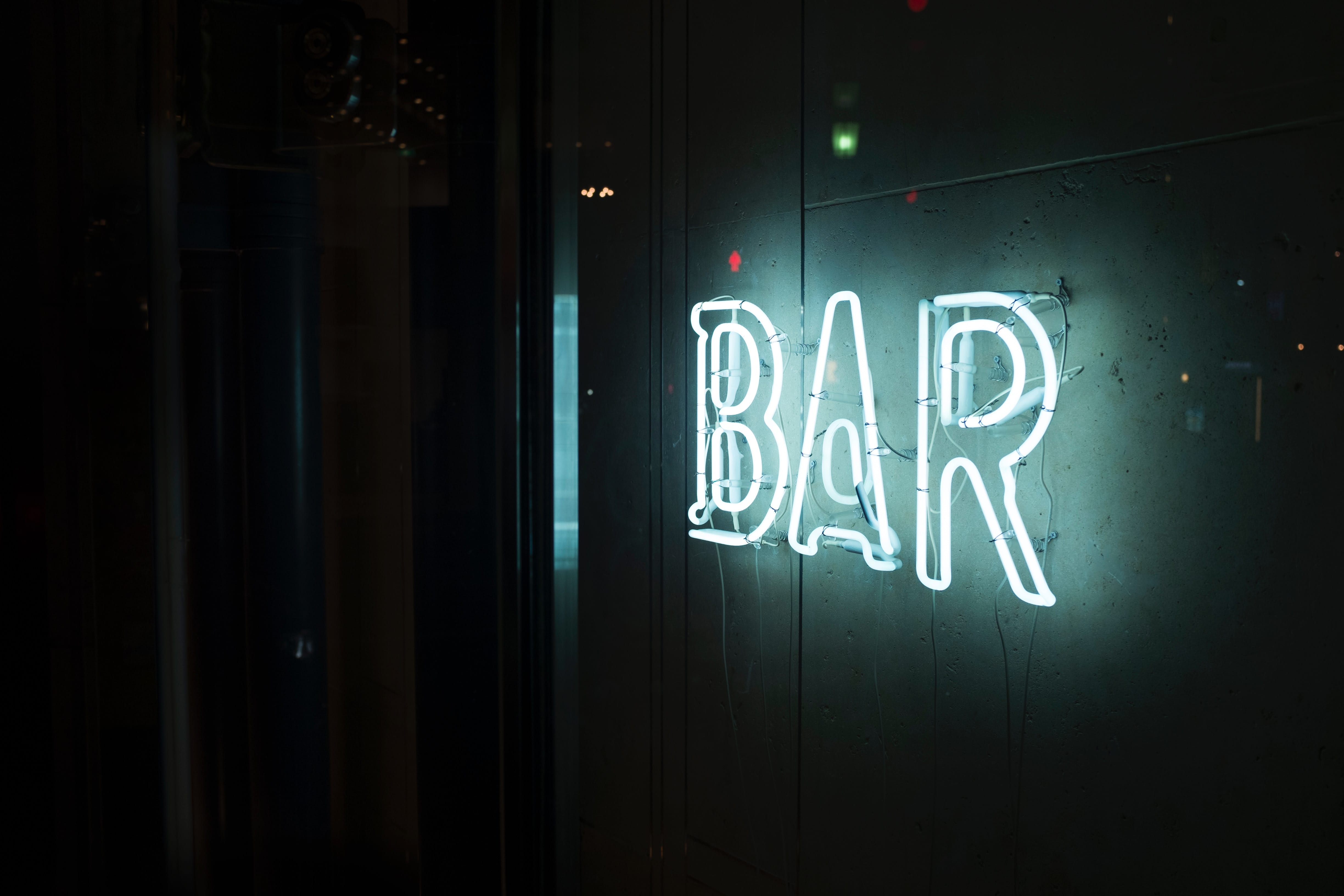 "Dark wall with white neon sign saying ""Bar""; image by Alex Knight, via Unsplash.com."