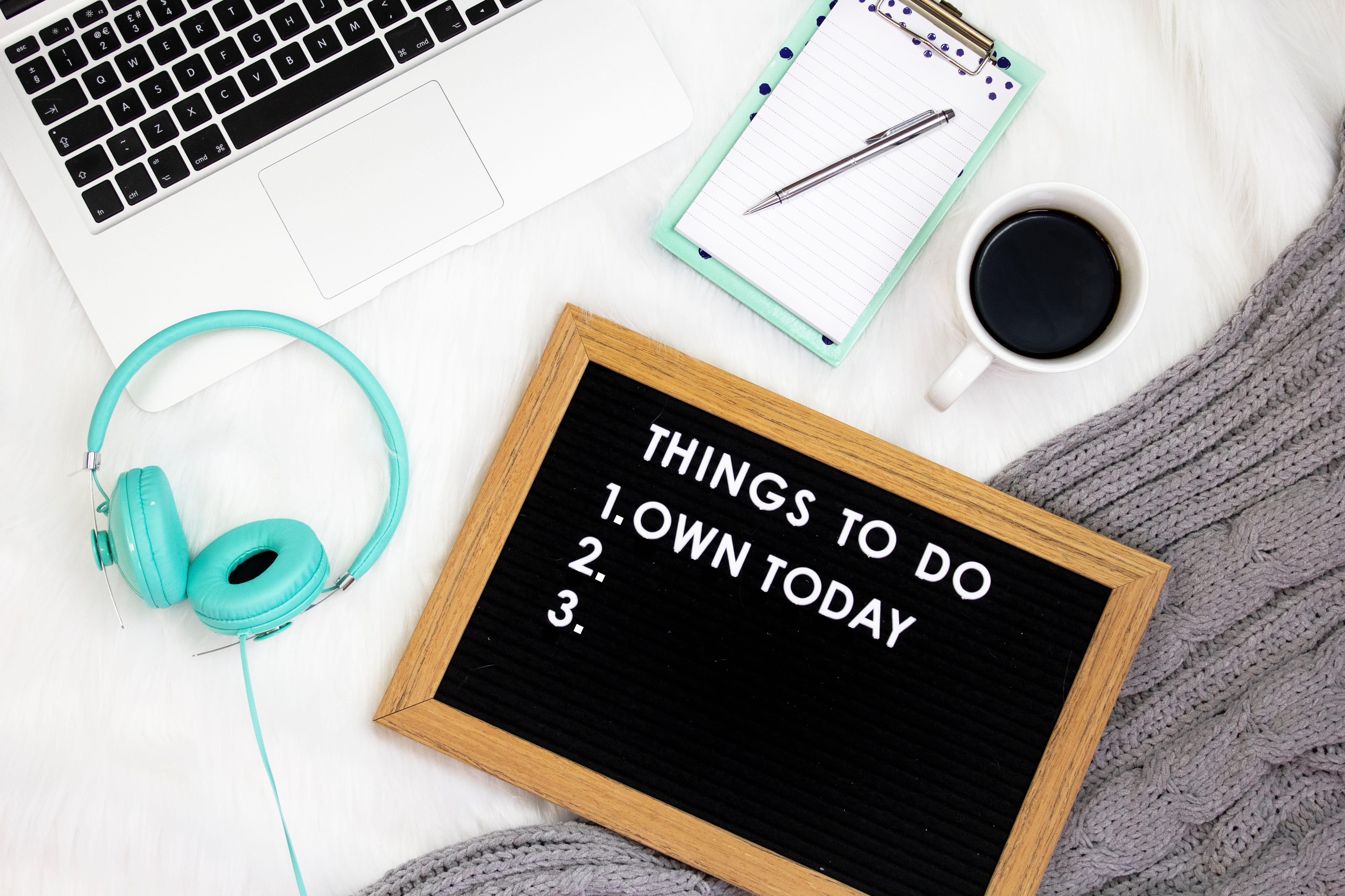 "Laptop, notepad, cup of coffee, and headphones on soft surface with sign reading ""Things to Do Today: Own Today."" Image by Emma Matthews, via Unsplash.com."