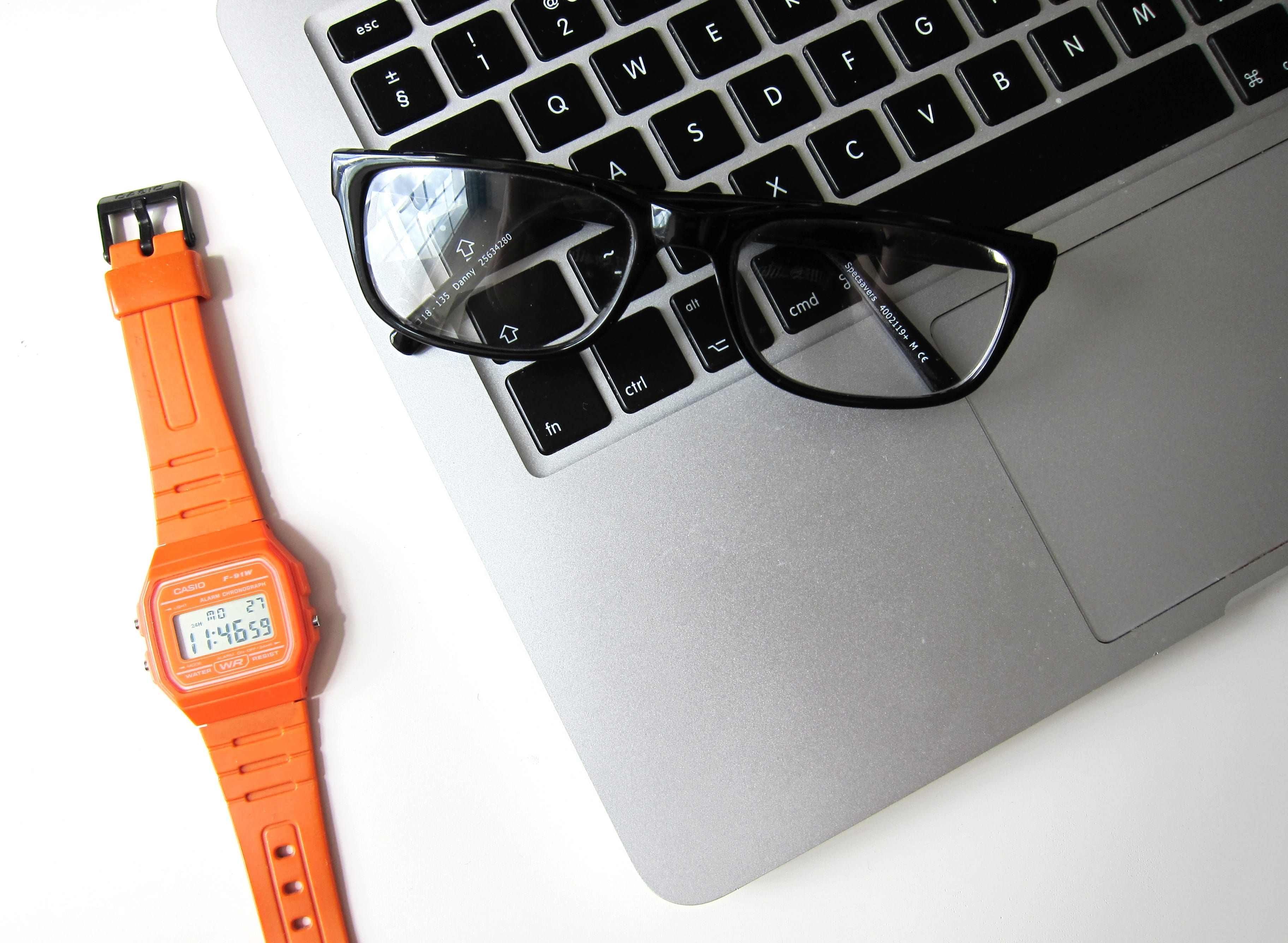 Reading glasses folded on a laptop along with a watch with orange band on a white desk; image by Hello I'm Nik, via Unsplash.com.