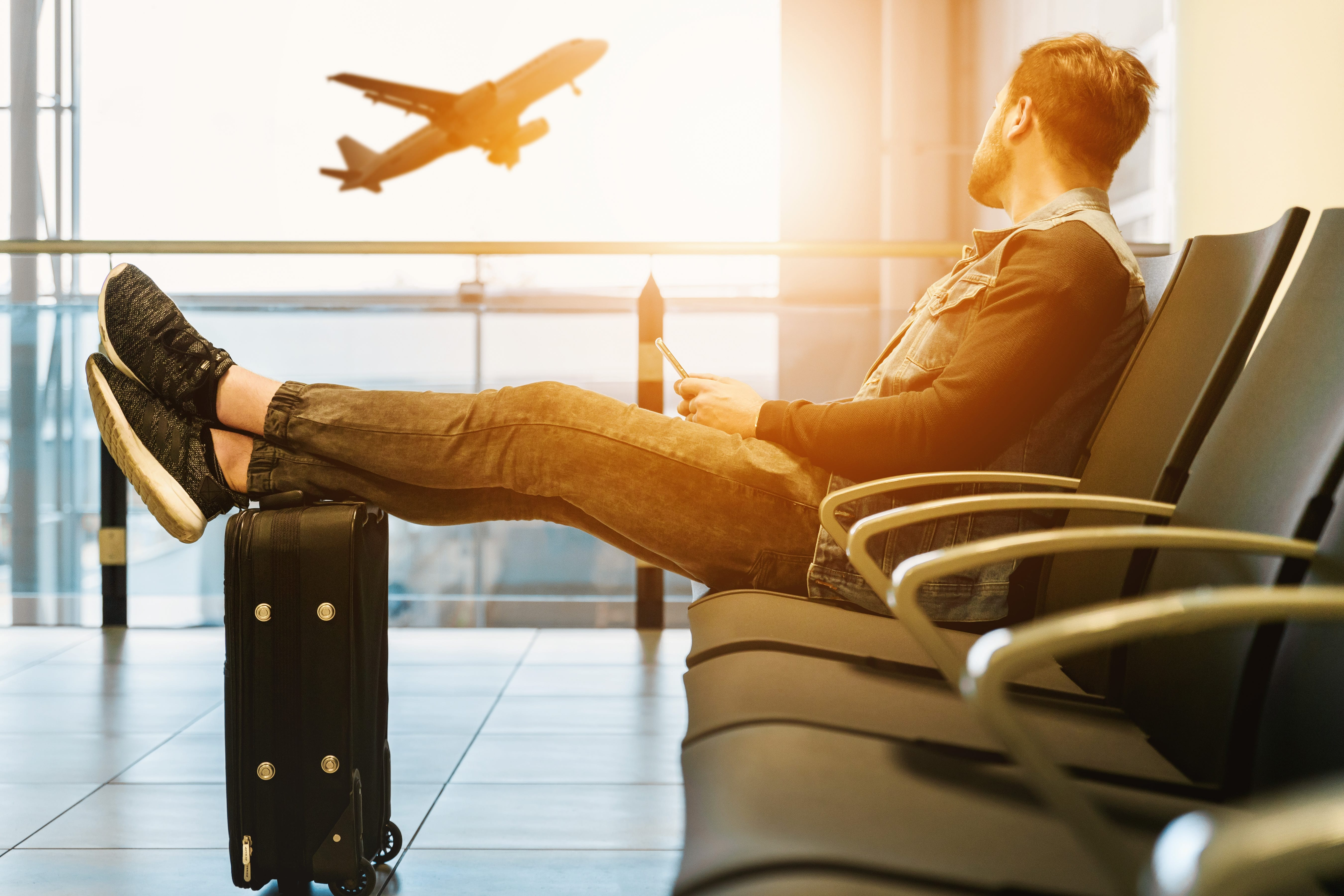 Man sitting on gang chair with feet on luggage looking at airplane; image by JESHOOTS.COM, via Unsplash.com.