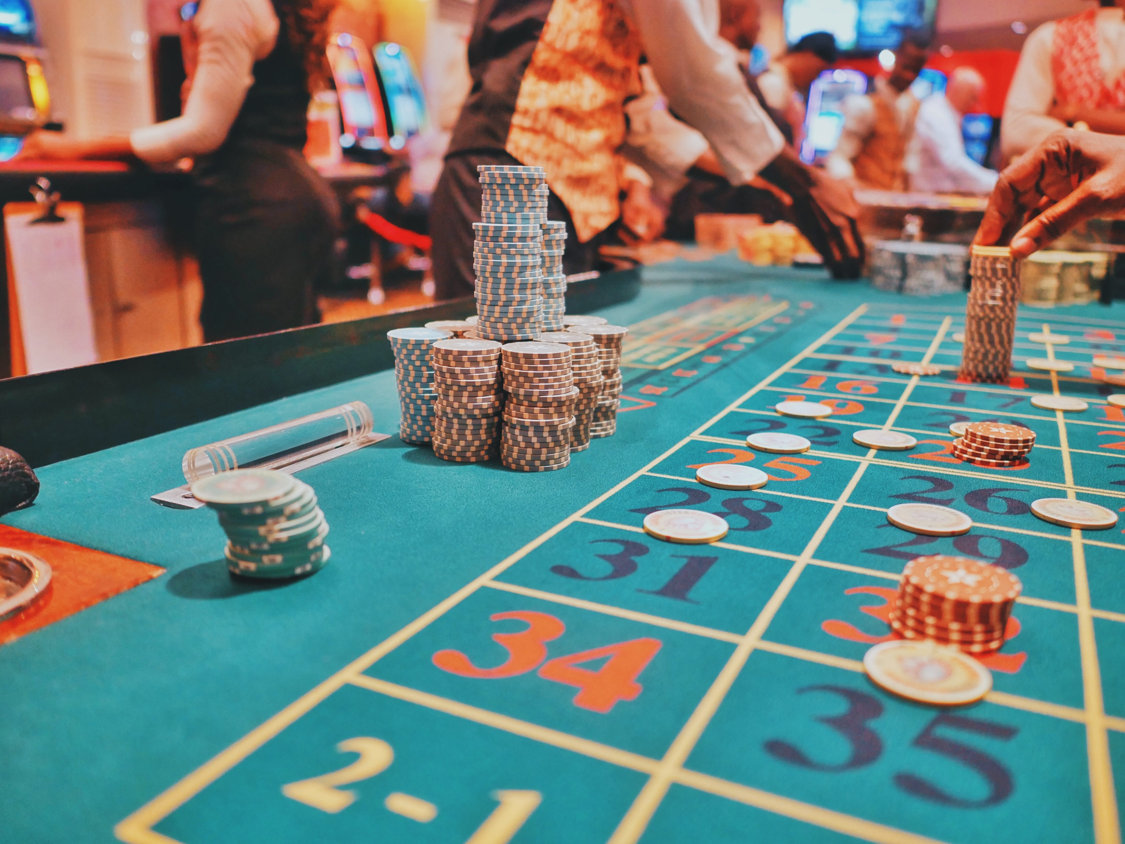 Gaming table with stacks of chips; image by Kay, via Unsplash.com.