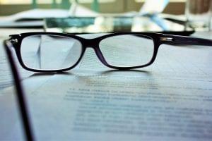 Reading glasses on paper; image by Mari Helin, via Unsplash.com.