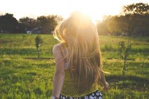 Blonde woman in grassy field facing sunshine; image by Morgan Sessions, via Unsplash.com.