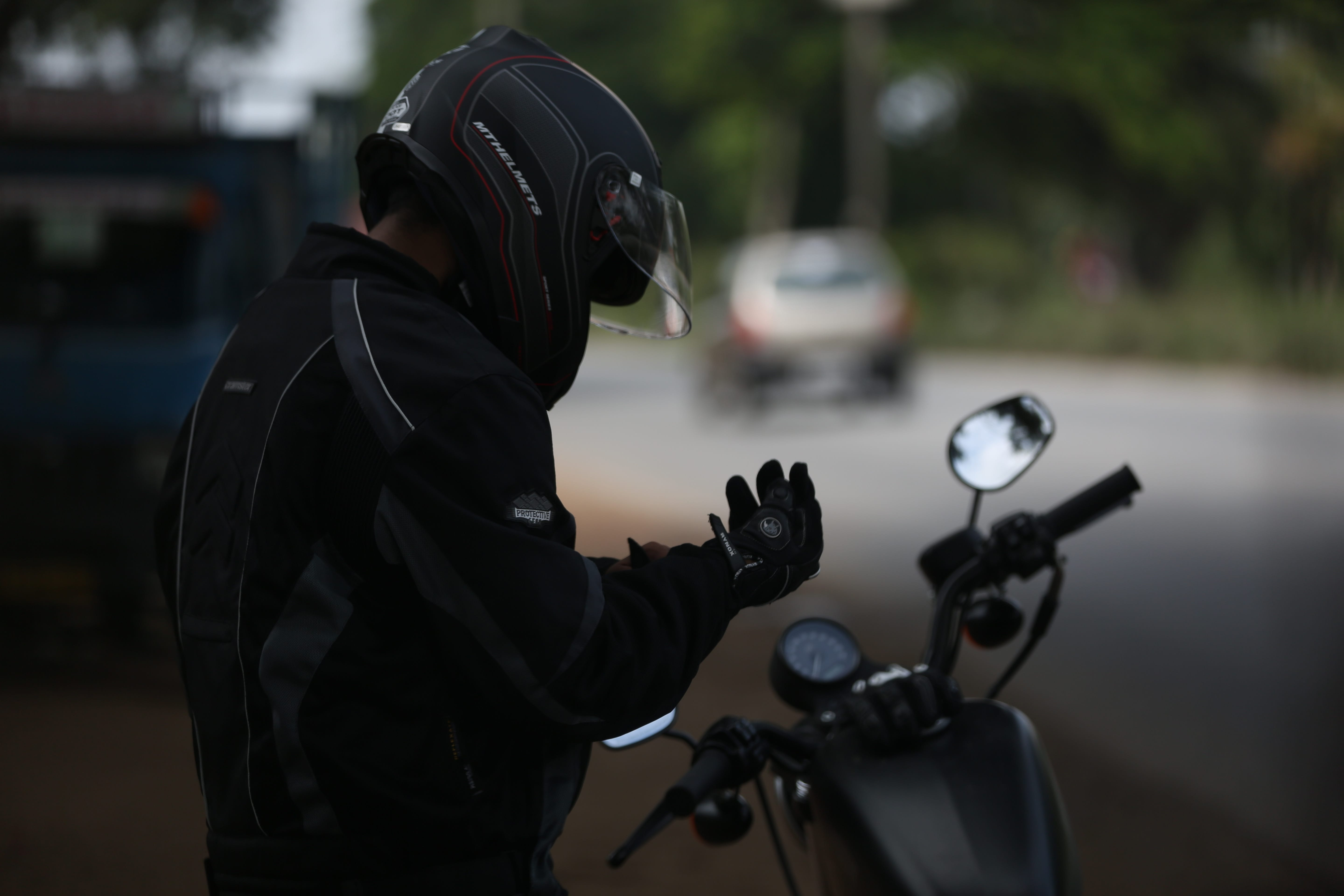 Selective focus shot of man in motorcycle suit sitting on motorcycle; image by Shajan Jacob, via Unsplash.com.
