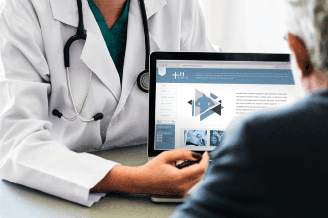 Doctor reviewing information on a laptop with patient; image by Rawpixels, via Pexels.com.