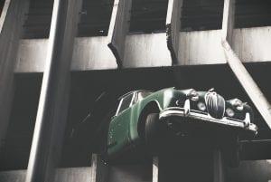 Green car extending outside parking garage after hitting barrier; image by Carafife, via Unsplash.com.
