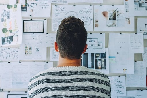 Man looking at project planning bulletin board; image by StartupStockPhotos, via Pixabay.com.