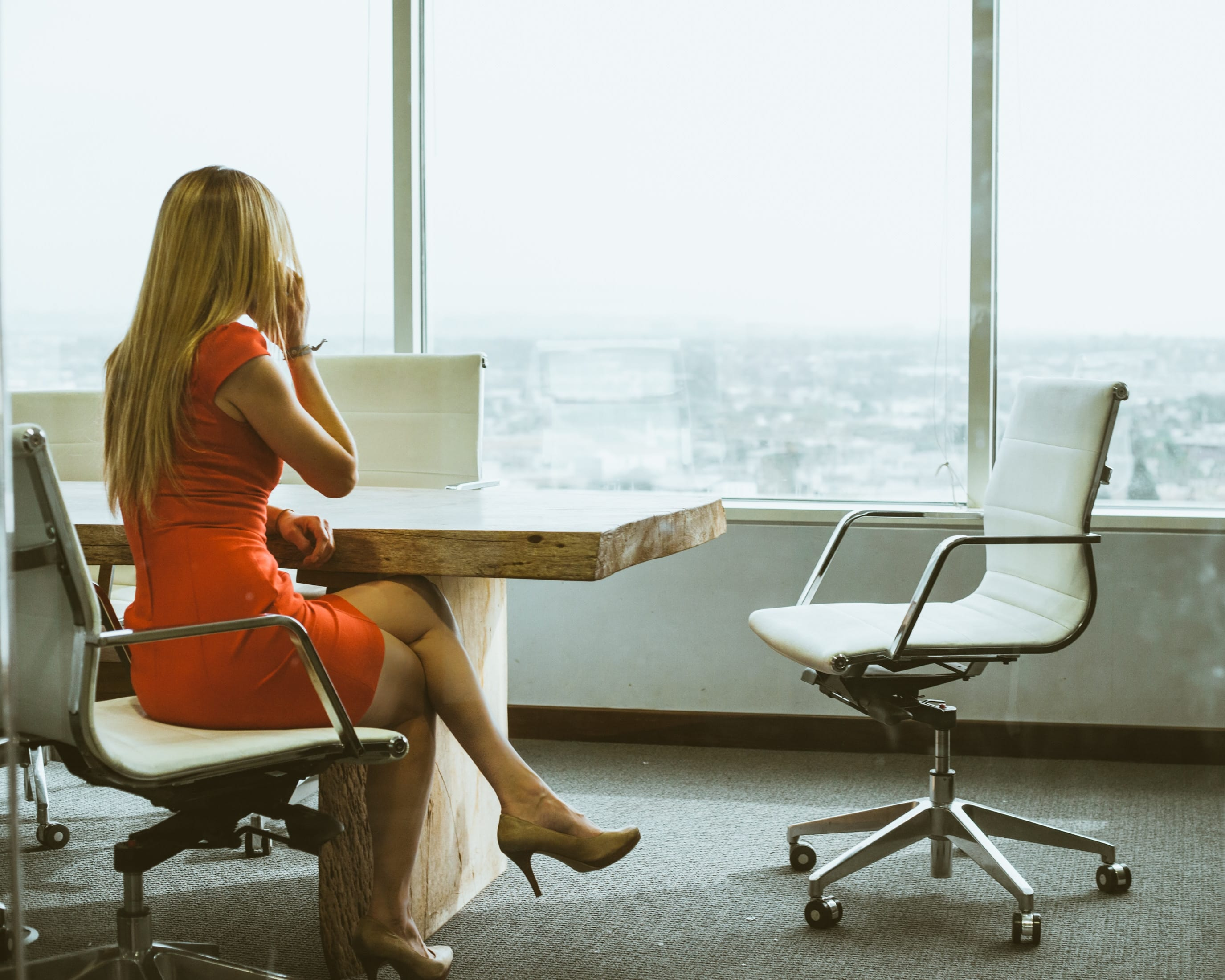 Woman in orange dress on cellphone sitting at conference room table looking out window; image by Dane Deaner, via Unsplash.com.