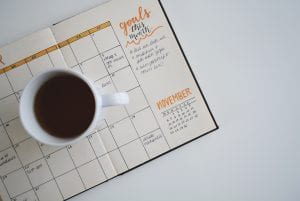 "Cup of coffee resting on planner open to November, ""Goals this month"" written in right margin; image by Estée Janssens, via Unsplash.com."