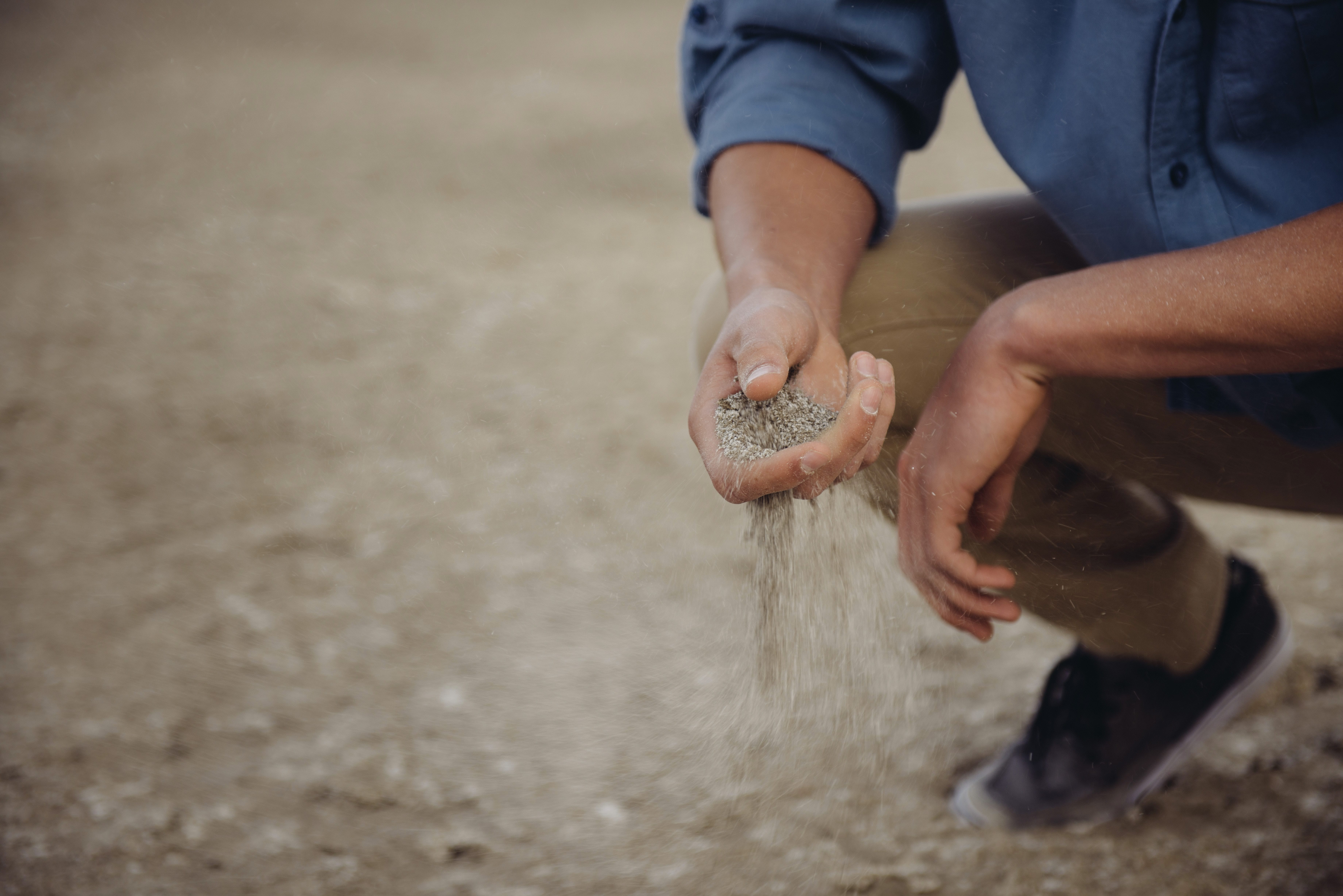 Man crouches down with a handful of sand that slips through his fingers; image by Forrest Cavale, via Unsplash.com.