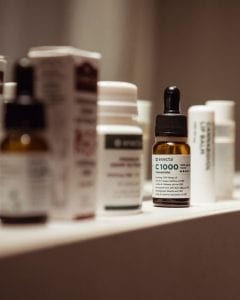 Shelf with bottles of medicine in soft focus and a bottle of CBD oil in clear focus; image by Francesco Mazzone, via Unsplash.com.
