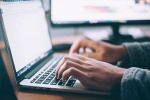 Man working at laptop; image by Glenn Carstens-Peters, via Unsplash.com.