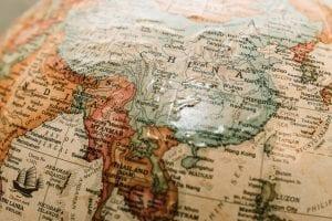 World globe with focus on China; image by James Coleman, via Unsplash.com.
