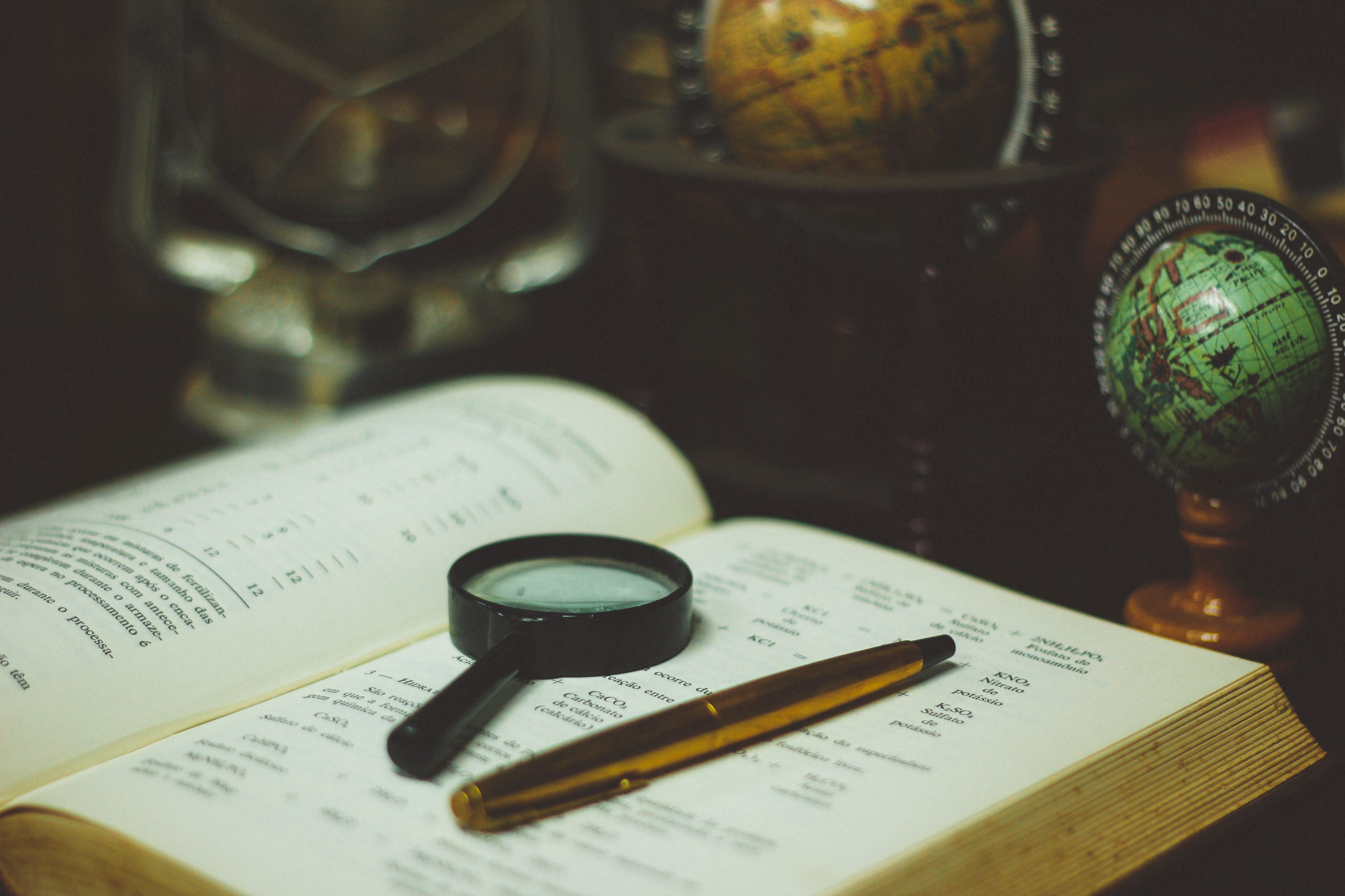 en and magnifying glass on open book sitting next to globes of the Earth; image by João Silas, via Unsplash.com.