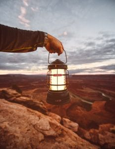 Person holding a camping lantern at dusk; image by Matthew Brodeur, via Unsplash.com.