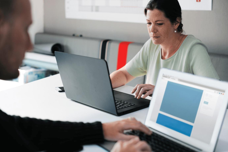 Man and woman using laptops; image by rawpixels.com, via Pexels.com.