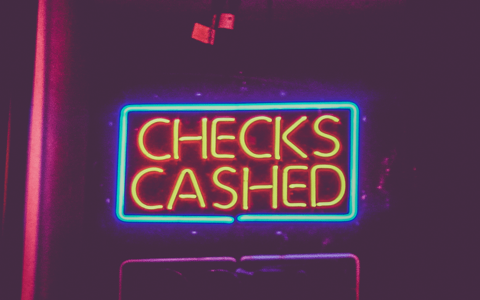 "Neon ""Checks cashed"" sign; image by Tony Webster from Oakland, California, CC BY 2.0, no changes."
