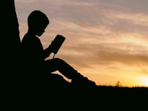 Silhouette of boy leaning against a tree at sunset, reading a book; image by Aaron Burden, via Unsplash.com.