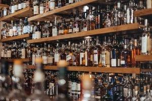 Assorted bottles of alcohol on a shelf; image by Adam Wilson, via Unsplash.com.