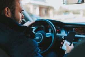 Driver using smartphone behind the wheel; image by Alexandre Boucher, via Unsplash.com.