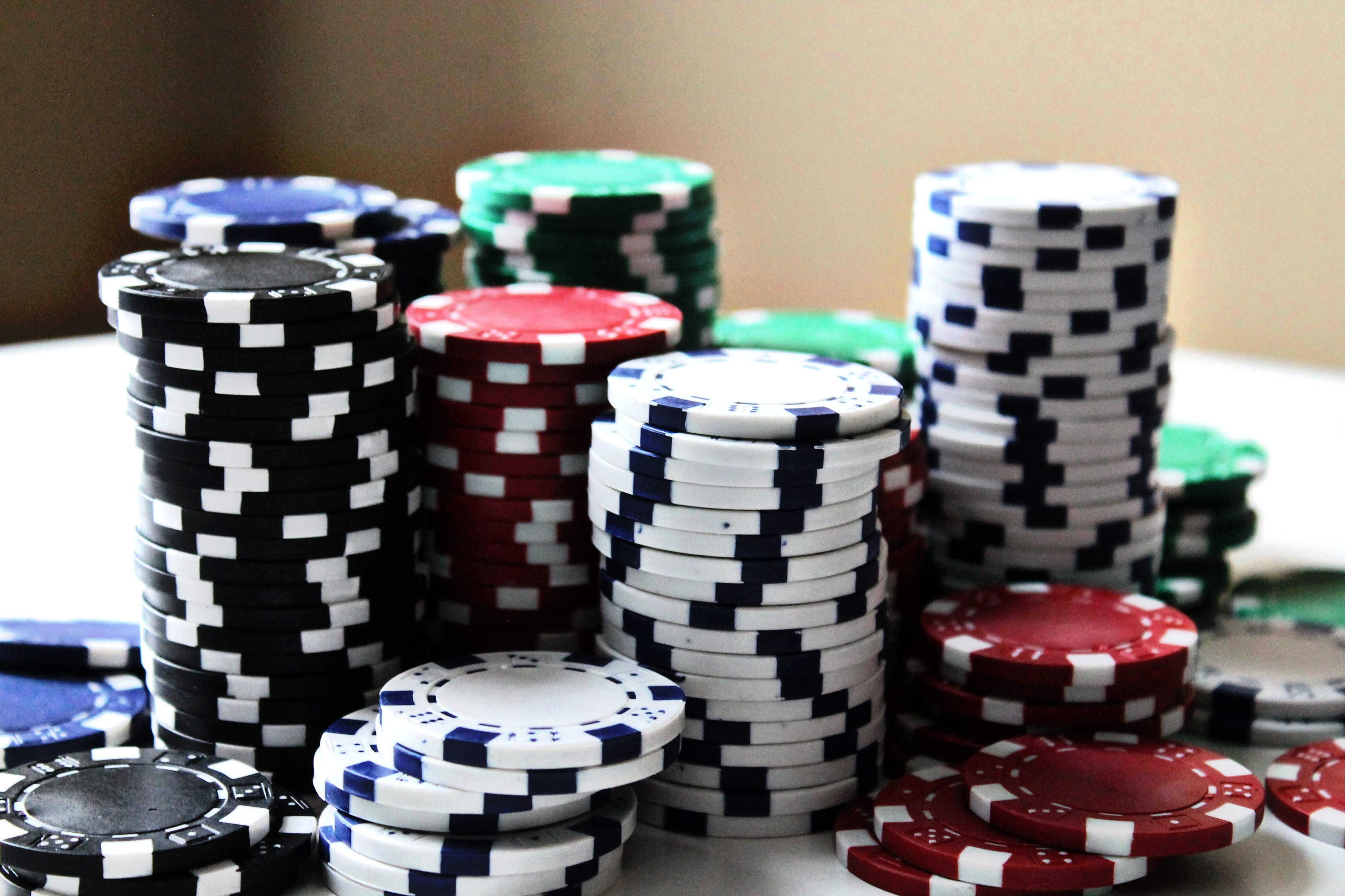Stacked poker chips of various colors; image by Amanda Jones, via Unsplash.com.