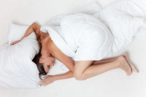 Woman curled up on all-white bed covered by white comforter; image by Pixabay, via Pexels.com.