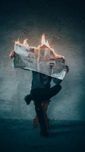 Man sitting on stool reading a newspaper that is on fire; image by Elijah O'Donnell, via Unsplash.com.