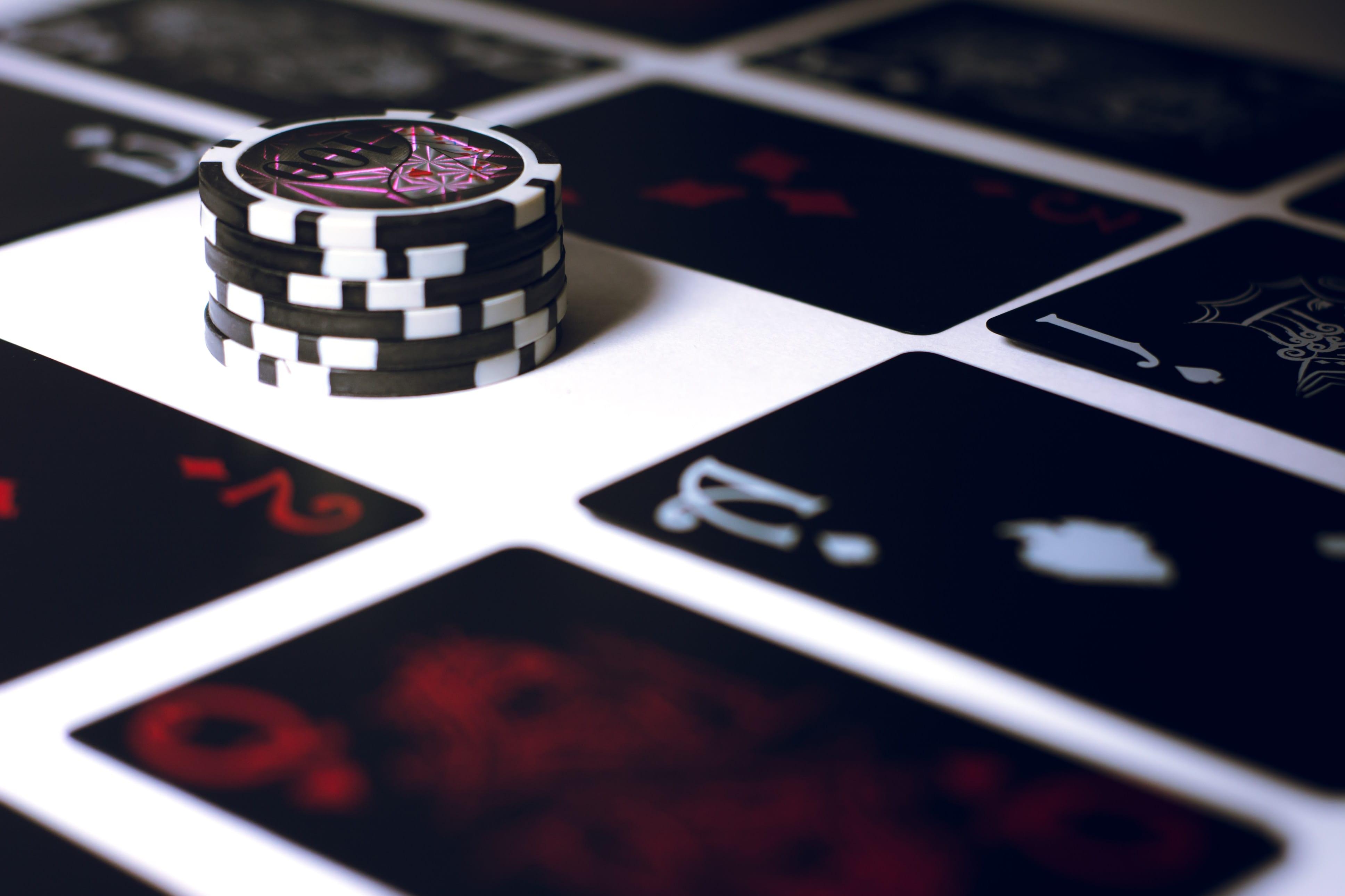 Poker chips on white surface; image by Esteban Lopez, via Unsplash.com.