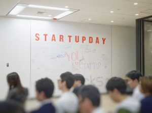"Soft focus of a group of people in a conference room with a white board saying ""Startupday."" Image by Franck V., via Unsplash.com."