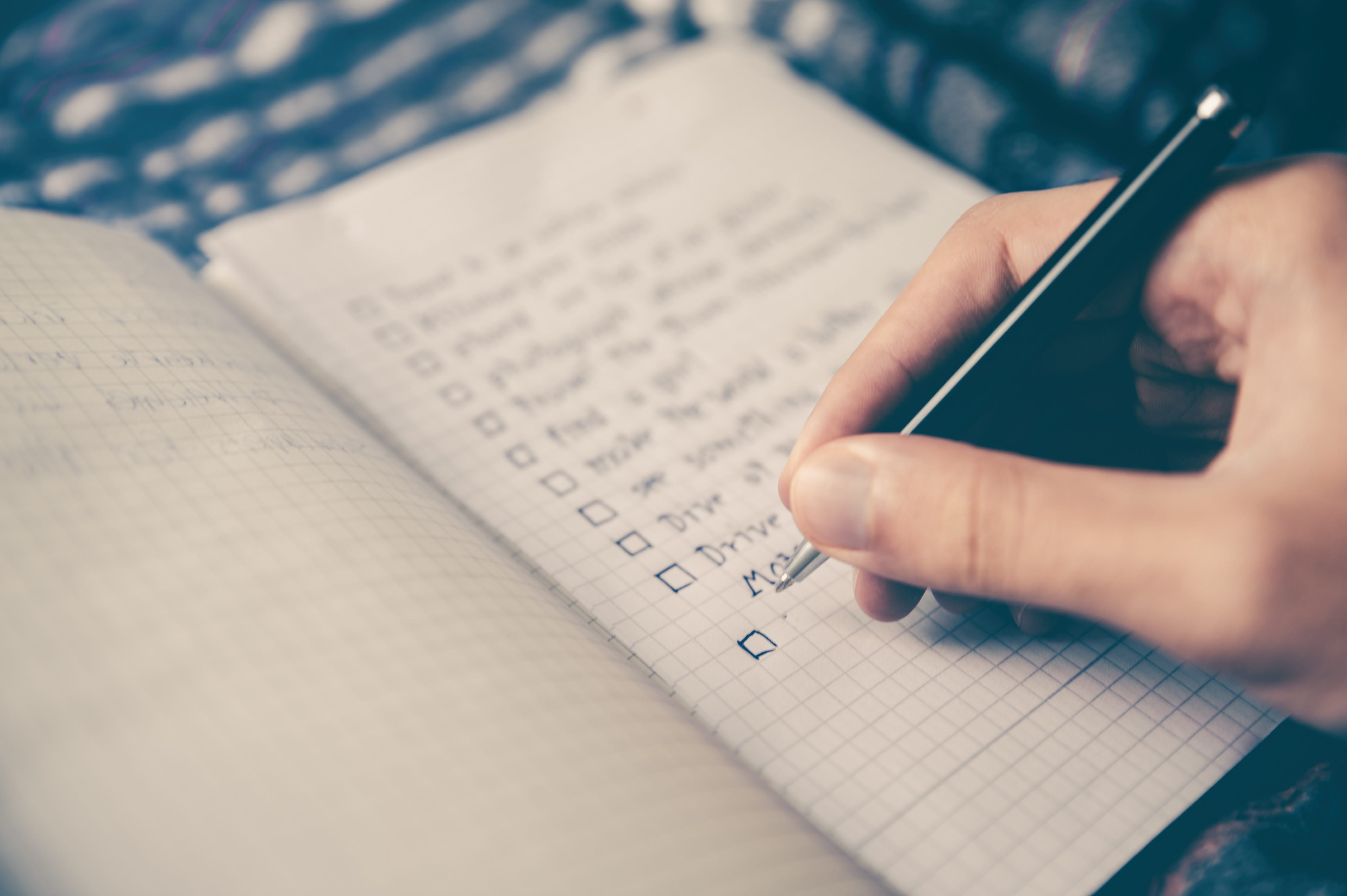 Person making a checklist of tasks; image by Glenn Carstens-Peters, via Unsplash.com.