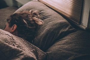Woman sleeping on brown bed linens; image by Gregory Pappas, via Unsplash.com.