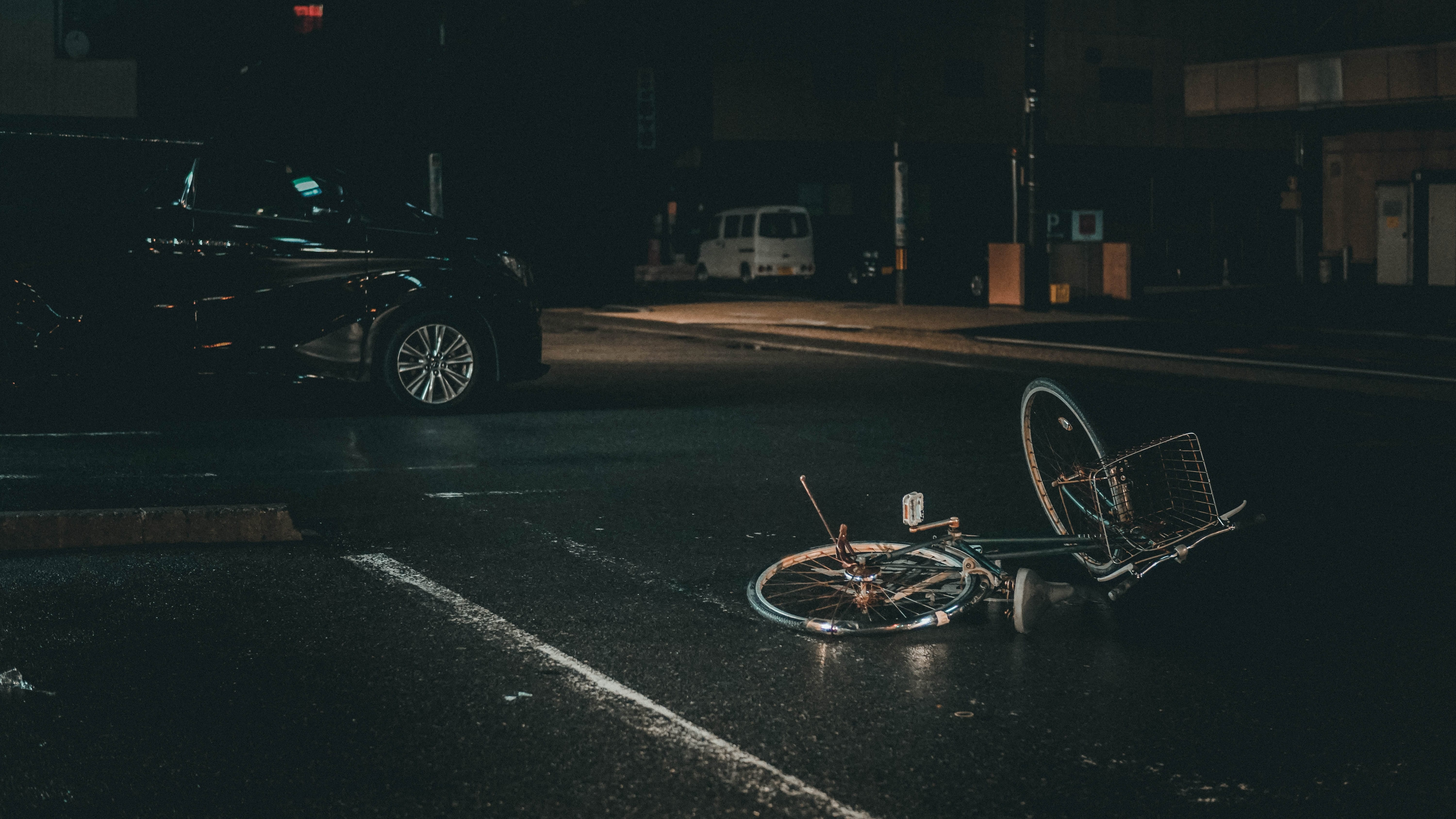 Bicycle on its side in the middle of a dark street with a car nearby; image by Ian Valerio, via Unsplash.com.