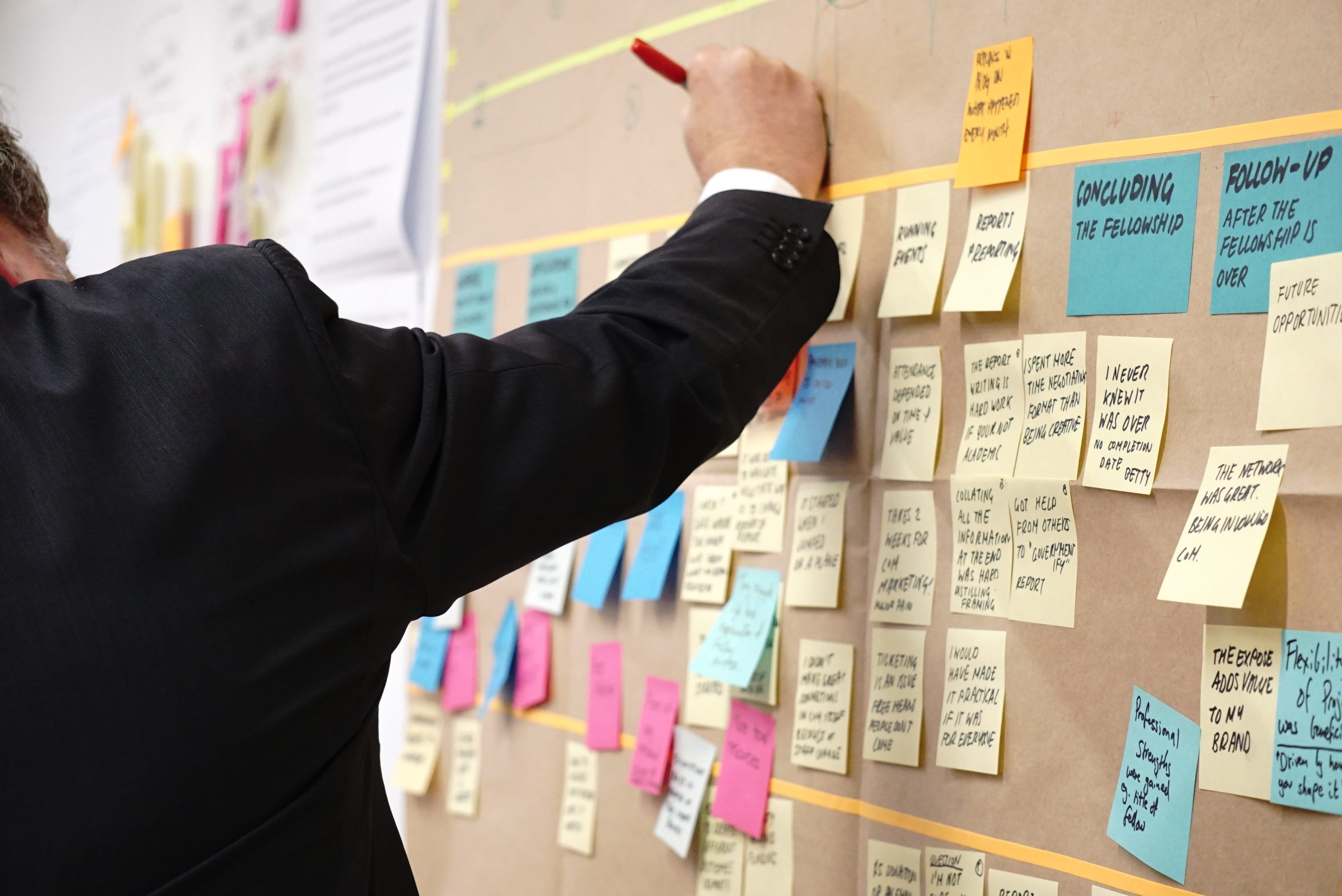Man working at a bulletin board full of sticky notes; image by Jo Szczepanska, via Unsplash.com.