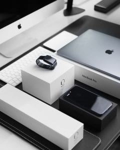 Space black case Apple Watch, silver MacBook Pro, jet black iPhone 7 Plus, and silver iMac with corresponding boxes; image by Julian O'Hayon, via Unsplash.com.