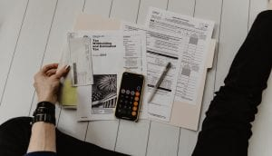 Woman in black pants sitting on floor with tax paperwork and a calculator; image by Kelly Sikkema, via Unsplash.com.
