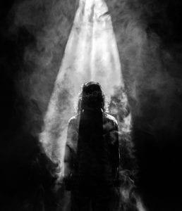 Person facing opposite in smoky spotlight; image by Mads Schmidt Rasmussen, via Unsplash.com.
