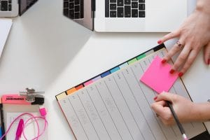 Woman holding pencil and sticky note on planner next to computer keyboard; image by Marten Bjork, via Unsplash.com.