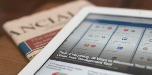Tablet sitting on top of financial section of newspaper; image by Matthew Guay, via Unsplash.com.